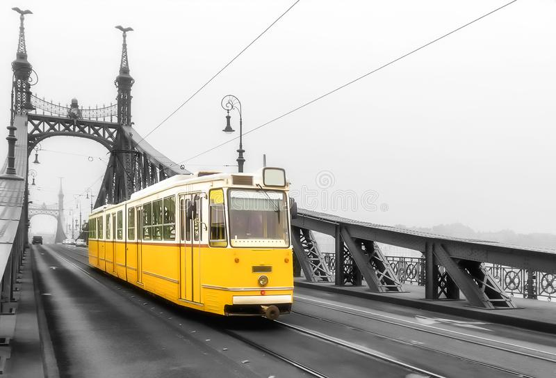 Gul retro spårvagn på Liberty Bridge i Budapest royaltyfria foton