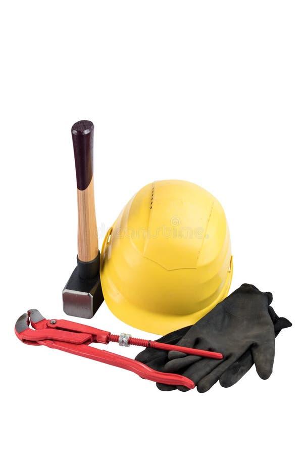 Gul säkerhetshjälm med en slägga med trähandtaget, funktionsdugliga handskar och justerbara rörmokareskiftnyckeln som isoleras på arkivfoto