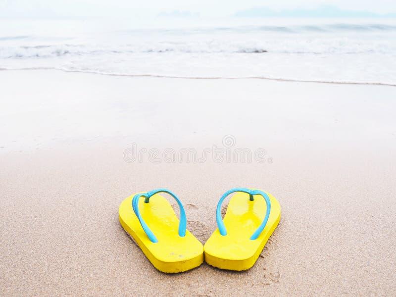 Gul sandal p? beige bakgrund f?r sandsommarstrand arkivfoto
