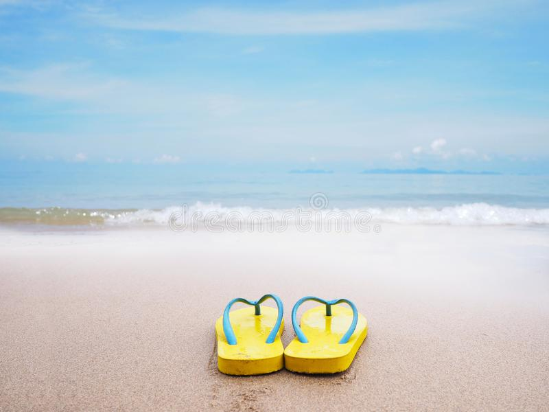Gul sandal p? beige bakgrund f?r sandsommarstrand arkivbild