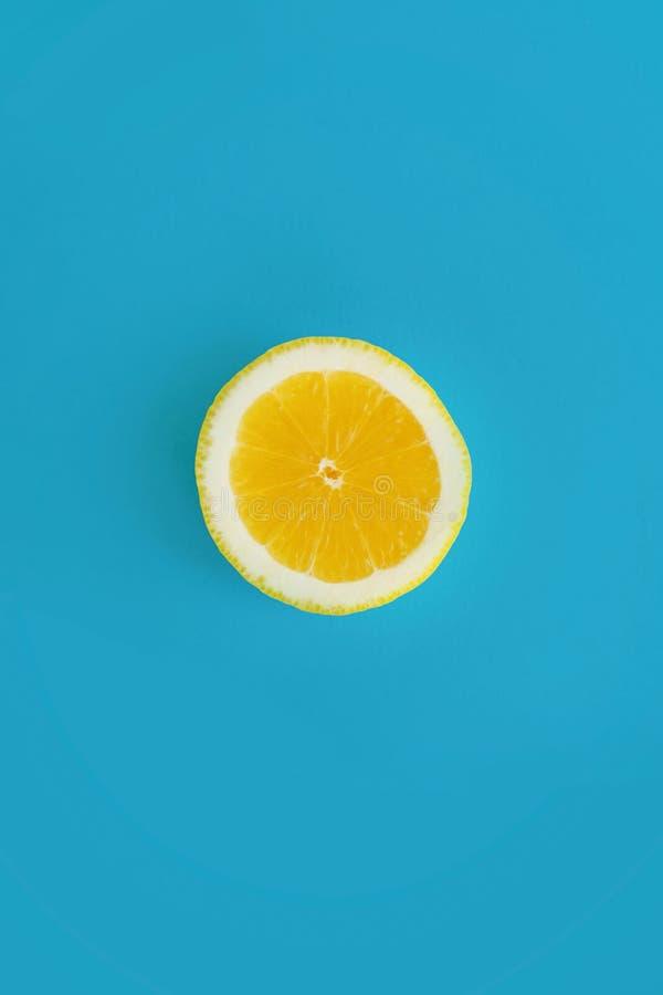 Gul skiva av citronen på ljust blått papper, lekmanna- moderiktig lägenhet Fru fotografering för bildbyråer
