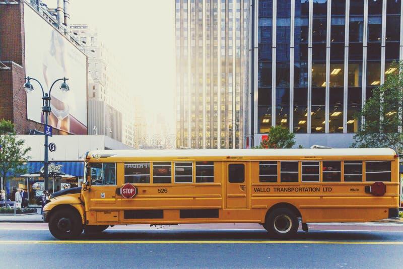 Gul skolbuss som kör längs en gata i Manhattan arkivfoto