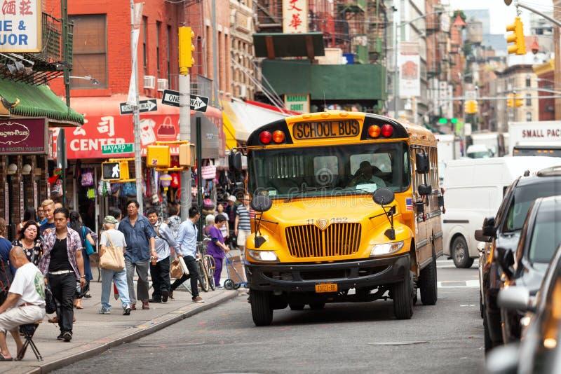 Gul skolbuss som kör till och med gatorna av kineskvarteret i New York royaltyfri foto