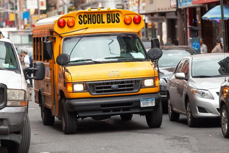 Gul skolbuss som kör till och med gatorna av kineskvarteret i New York arkivbild