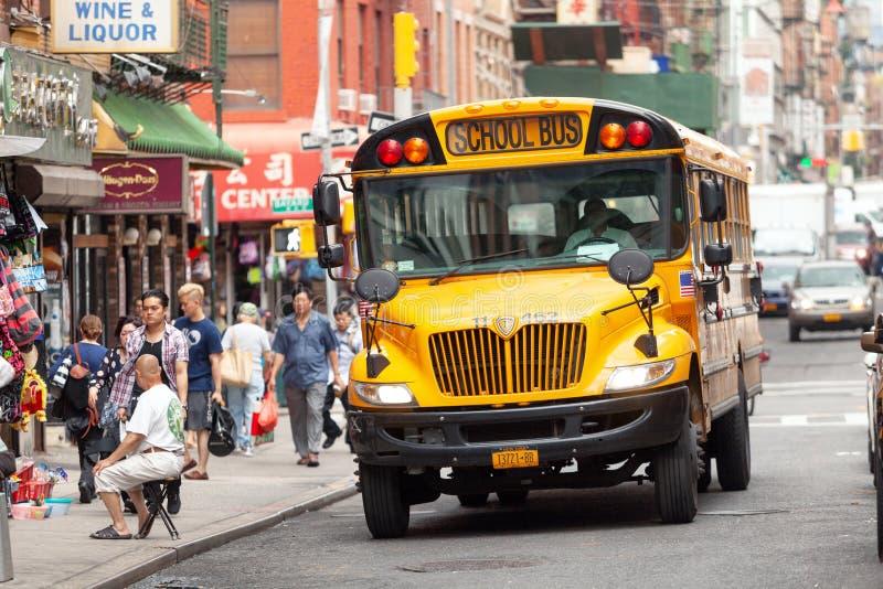 Gul skolbuss som kör till och med gatorna av kineskvarteret i New York royaltyfri bild