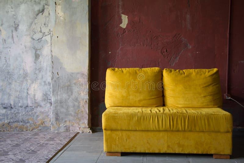 Gul soffa över väggen för röd tegelsten i en vindstilstudio, minimalismmöblemangbegrepp, fotostudioinre arkivbilder