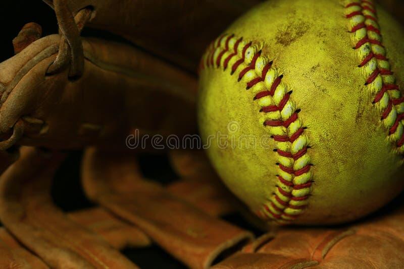 Gul softballcloseup med röda sömmar på en brun läderhandske arkivfoton