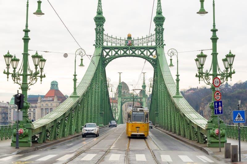 Gul spårvagn på Liberty Bridge i Budapest, Ungern royaltyfria bilder