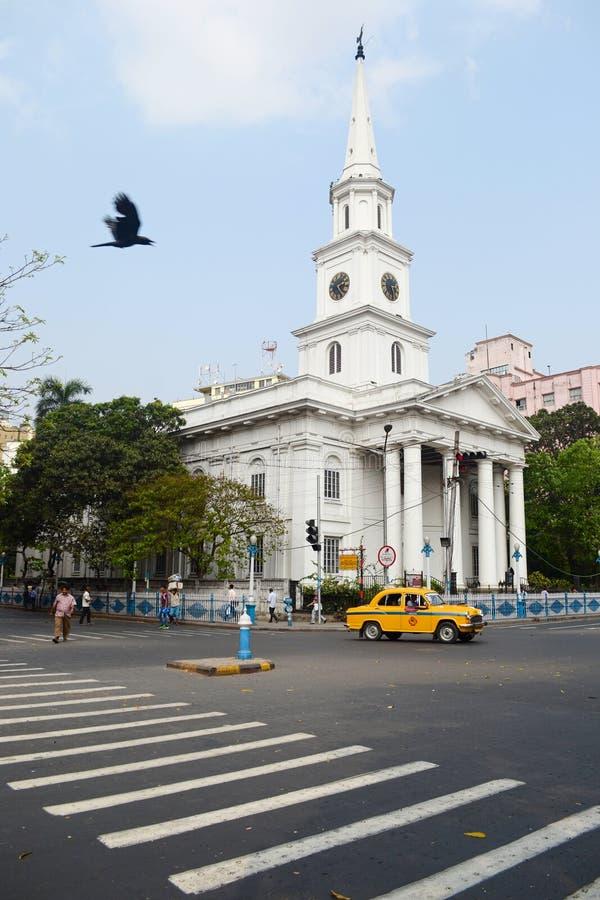 Gul taxi på vägen framme av katolska kyrkan royaltyfri bild