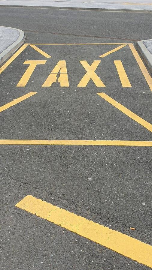 Gul taxi som parkerar tecknet på en gata royaltyfri bild