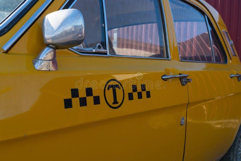 Gul taxibilcloseup krombest?ndsdelar av bilkroppen 60-70 ?r royaltyfri bild