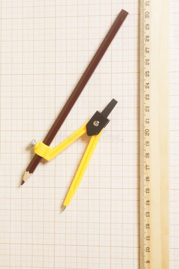 Gul teckningskompass med den svarta blyertspennan och linjal på graf arkivbild
