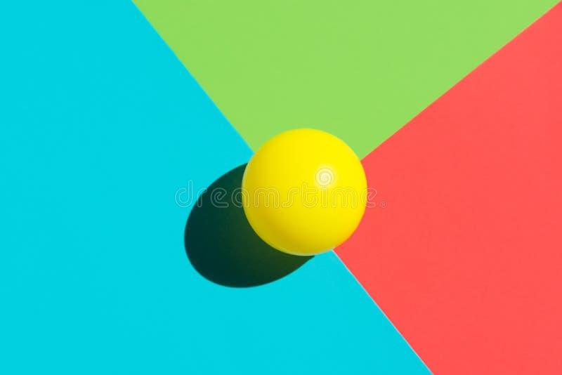 Gul tennisboll på blåa röda gröna triangelbeståndsdelar Abstrakt färgrik grafisk geometrisk sammansättning Affärsinnovation arkivbild