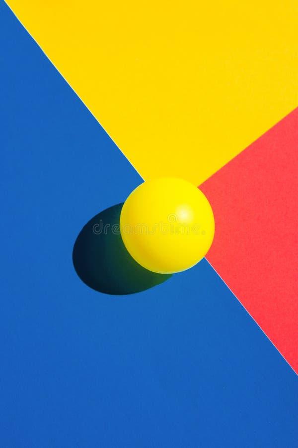 Gul tennisboll på blåa röda polygonformbeståndsdelar Abstrakt färgrik grafisk geometrisk sammansättning Affärsinnovation arkivfoton
