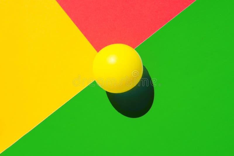 Gul tennisboll på grön röd triangelgenomskärning Abstrakt färgrik grafisk geometrisk bakgrund Aff?rsinnovation royaltyfri bild
