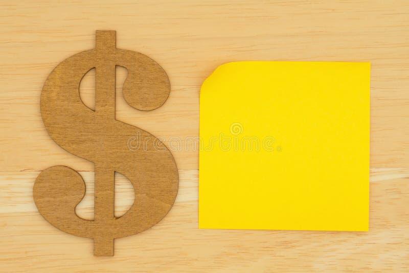 Gul tom klibbig anmärkning med ett dollartecken på det texturerade träskrivbordet royaltyfria foton