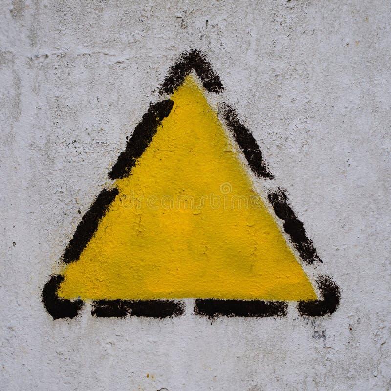 Gul triangel, fyrkant, romb i svart prickig ram på den gamla gemensamma väggen arkivfoton