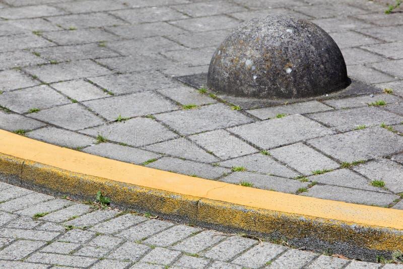 Gul trottoarkant och hinder arkivbild