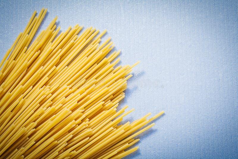 Gul tunn spagetti på blått bakgrundsmat och drinkbegrepp royaltyfri fotografi