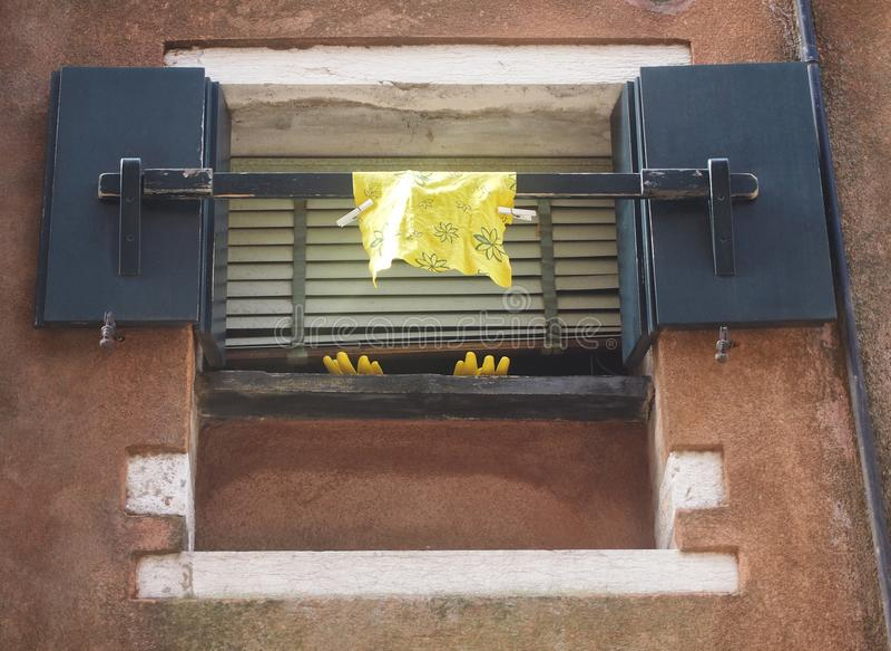 Gul tvätt upp handskar och torkduken som hänger ut ur ett fönster royaltyfri fotografi