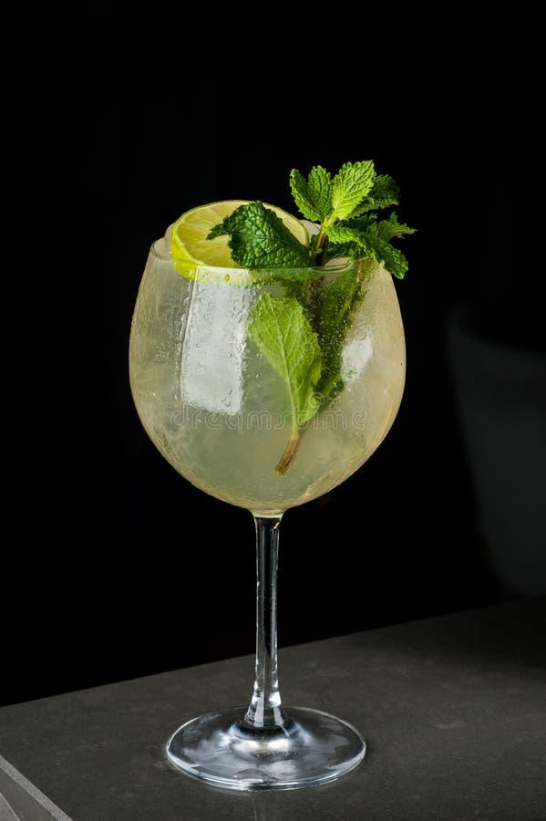 Gul uppfriskande drink med citronen och mintkaramellen i ett exponeringsglas av is royaltyfri fotografi