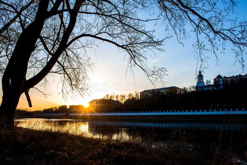 Gul varm solnedg?ng p? bankerna av Uralsna och mot invallningen av staden av Orenburg arkivbilder