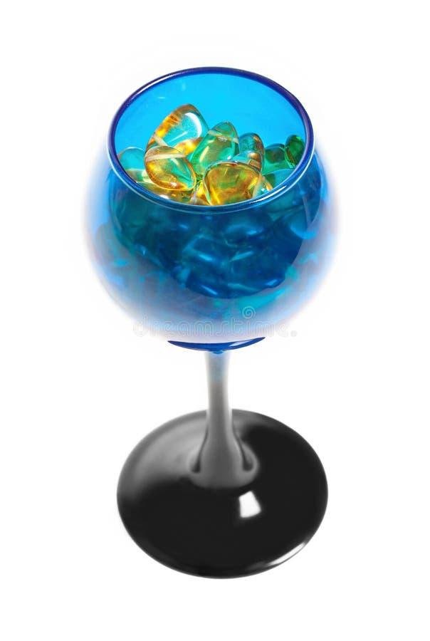 Gula bärnstenstenar i det blåa exponeringsglaset för vin royaltyfri foto