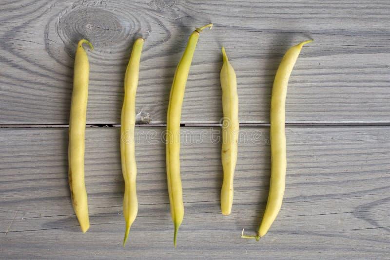 Gula bönor på en grå trätabell royaltyfria bilder