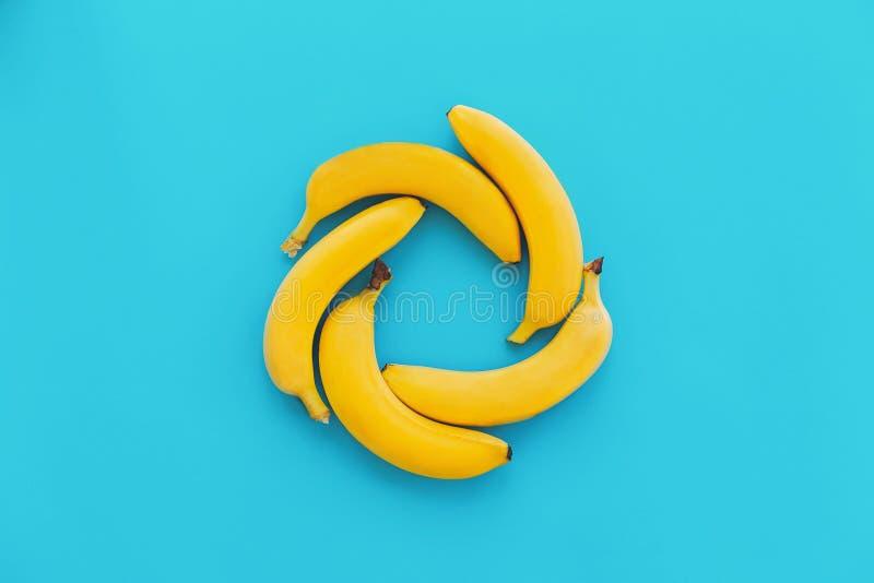 Gula bananer i cirkel på moderiktig bakgrund för blått papper, lägenhet arkivbilder