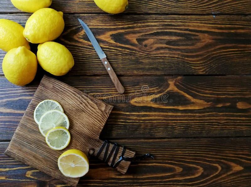 Gula citroner med en kniv högg av på skärbrädan på gammal träbakgrund arkivbilder
