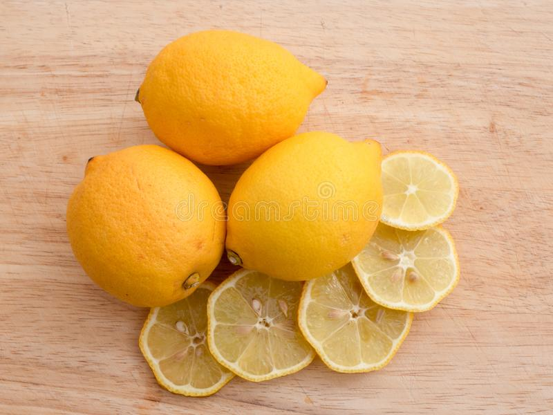 Gula citroner på en träskärbrädabakgrund royaltyfri foto