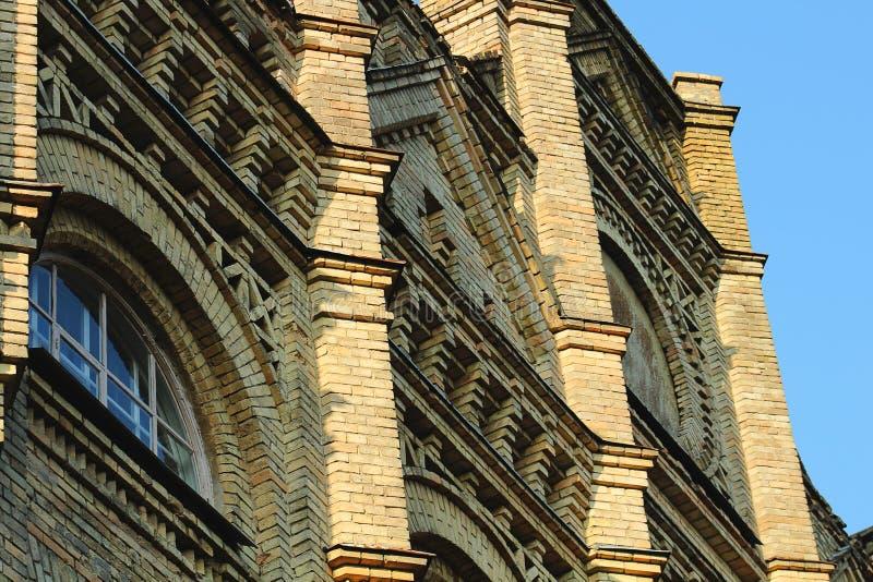 Gula fönster för tegelstenuniversitetbyggnad fotografering för bildbyråer