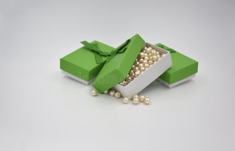 Gula guld- bollpärlor för elfenben i den gröna gåvaasken med två andra gröna gåvaaskar med pilbågen arkivfoton