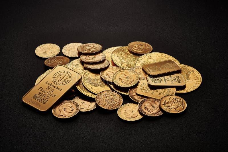 Gula guld- stänger och mynt som isoleras på svart bakgrund arkivbild