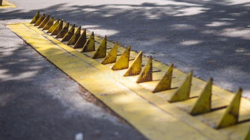 Gula gummihjulgrova spikar på tillträdeet av en parkeringsplats royaltyfri bild