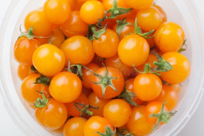 Gula körsbärsröda tomater i behållaren royaltyfria foton