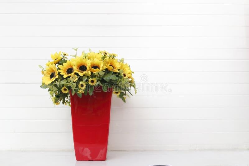 Gula konstgjorda blommor i röd vas med vit bakgrund royaltyfria foton