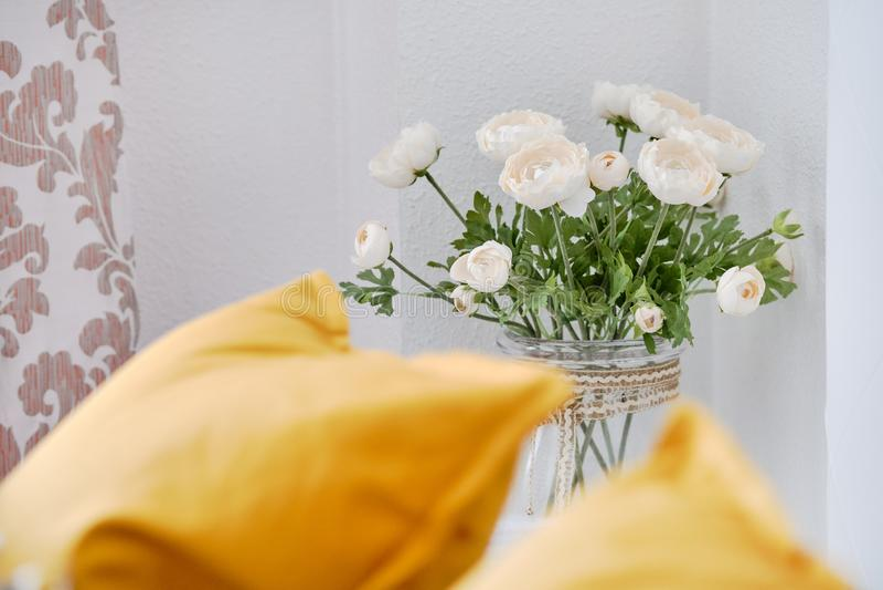 Gula kuddar p? soffan i vardagsrum, fokus p? h?rliga blommor i den vita ranunculusen f?r vas n?ra gullig garnering f?r v?gg hemma royaltyfri foto