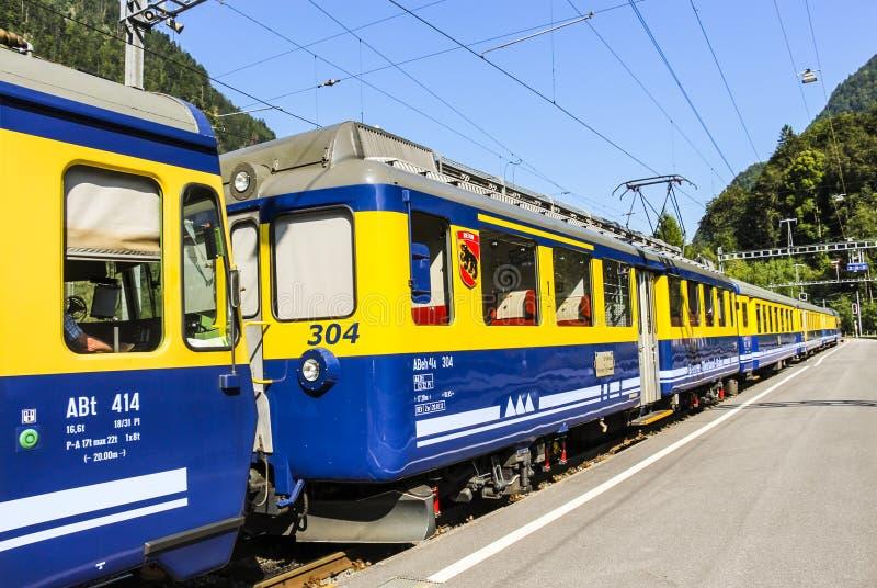 Gula och blåa Bernese Oberland järnväg drevstopp på plattformen för Grindelwald drevstation royaltyfri fotografi