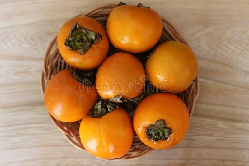 Gula och mogna persimoner på en sugrörplatta arkivfoton