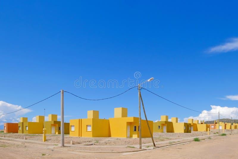 Gula och orange kulöra radhus, alla terrasserade hus byggde i den samma stilen, Chilecito, La Rioja, Argentina royaltyfria bilder