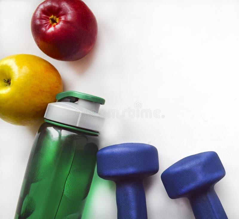 Gula och röda äpplen, en grön vattenflaska och två blåa hantlar på en vit bakgrund royaltyfri bild