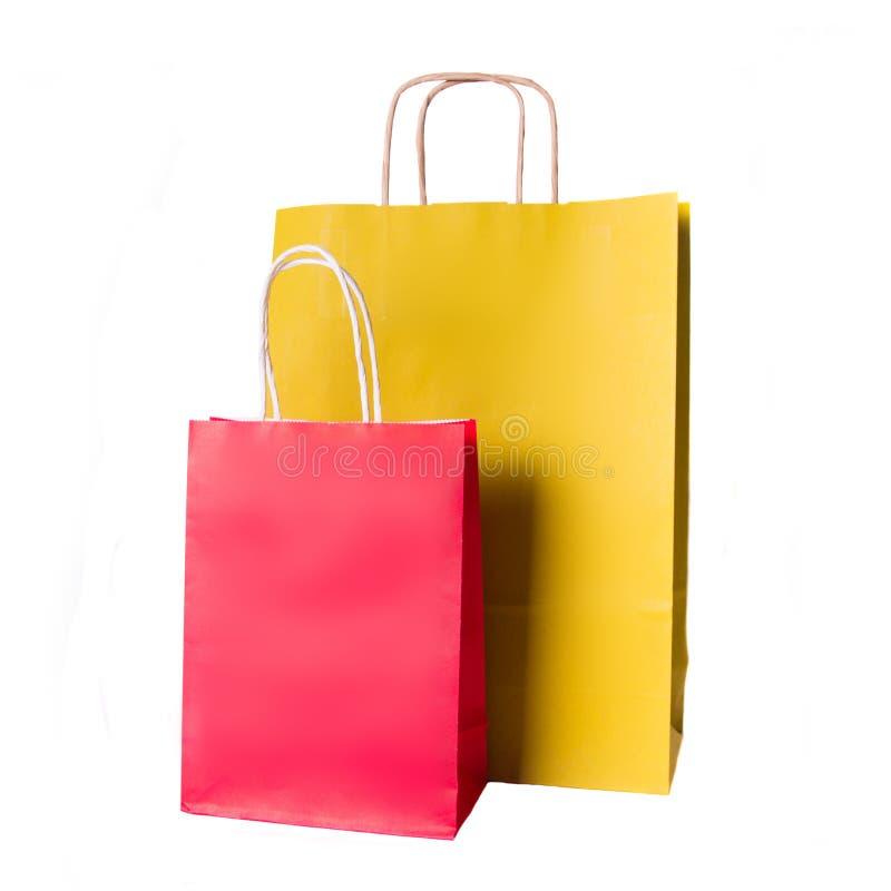 Gula och röda pappers- shoppa påsar som isoleras på vit arkivfoto