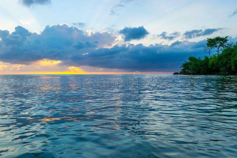 Gula, orange, rosa blåa himlar exponerade som solstrålar som brists till och med molnen på solnedgången royaltyfria bilder