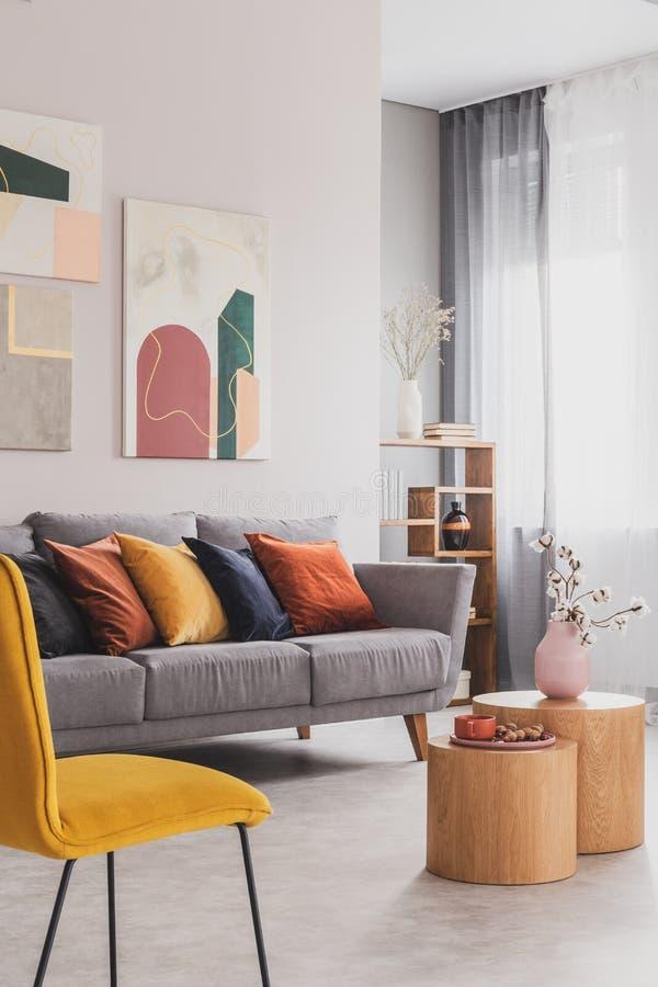 Gula, orange, svarta och bruna kuddar på den bekväma gråa scandinavian soffan i ljus vardagsrum som är inre med abstrakt begrepp royaltyfri fotografi