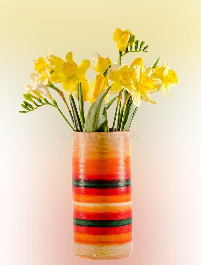 Gula påskliljor och freesiablommor i en livlig kulör vas, slut upp som isoleras, lutningbakgrund arkivfoto