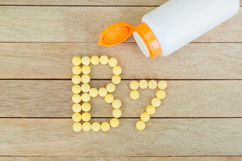 Gula preventivpillerar som bildar form till alfabetet B7 på wood bakgrund royaltyfri fotografi