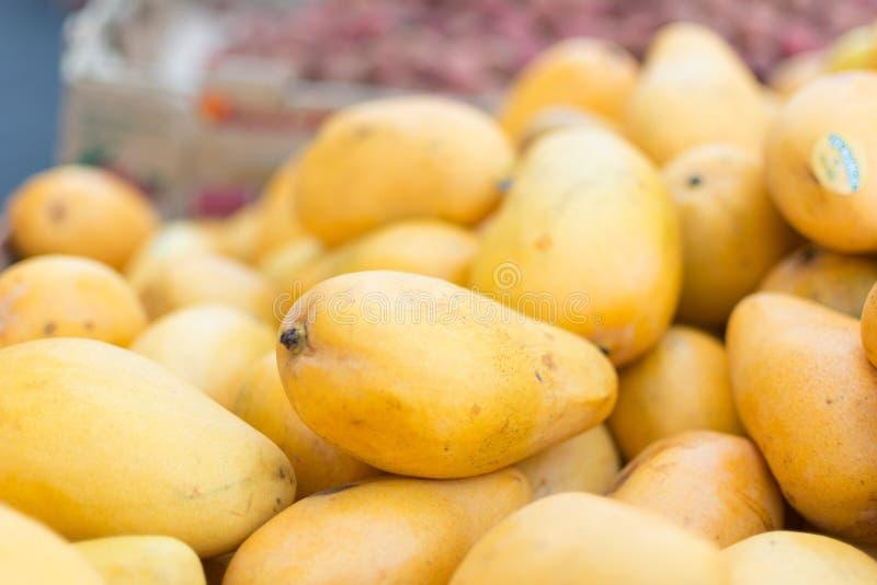 Gula saftiga mango i marknad royaltyfri bild
