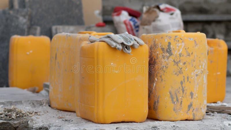 Gula smutsiga kanistrar på jordningen royaltyfri fotografi