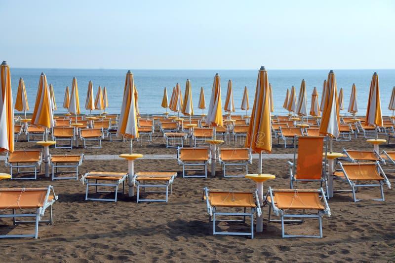 gula solparaplyer och deckchairs på den sandiga stranden av ret royaltyfria foton